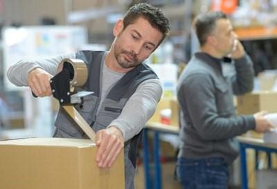 Mann klebt Paket mit PVC Klebeband